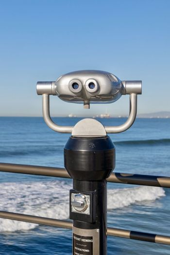 coin operated viewer overlooking the ocean Water Binoculars Sea Coin Operated Sky Railing Coin-operated Binoculars Nature Clear Sky Day Metal No People Security Surveillance Close-up Beauty In Nature Outdoors Blue Scenics - Nature Horizon Over Water Silver Colored Vacations Beach Travel Destination