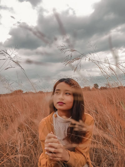 Young woman looking away while sitting on land against sky