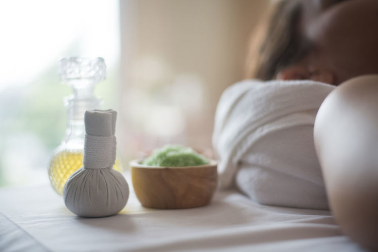 Young woman lying by ice pack and oil on massage table in spa