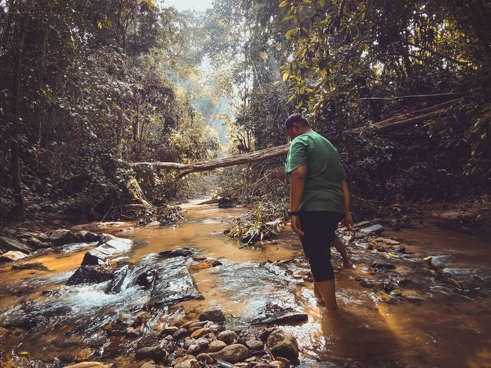 Side view of man standing in river at forest