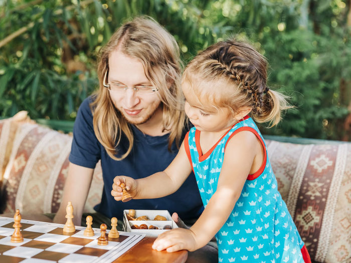 Smiling man sitting by daughter playing chess on table