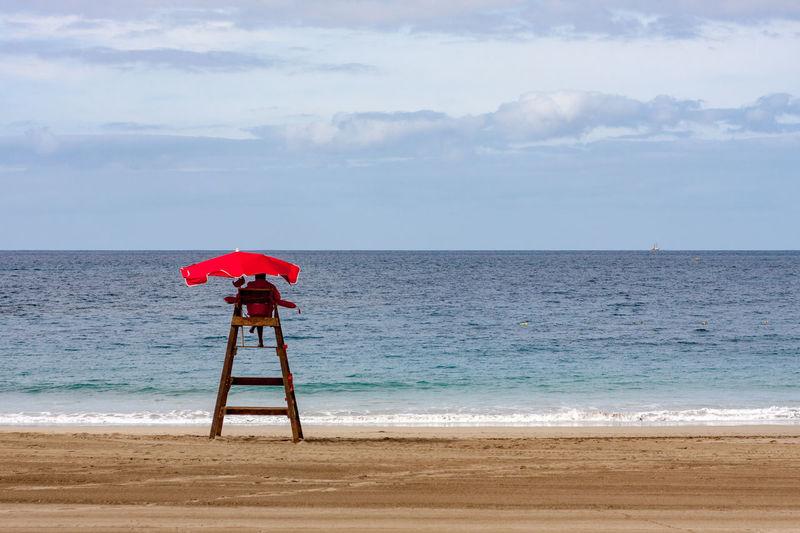 Lifeguard chair on beach against sky
