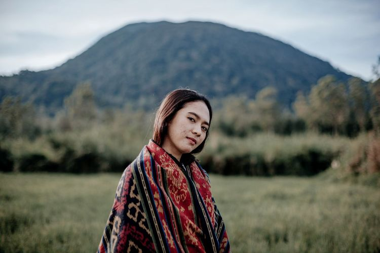 Portrait of woman standing on field against mountains