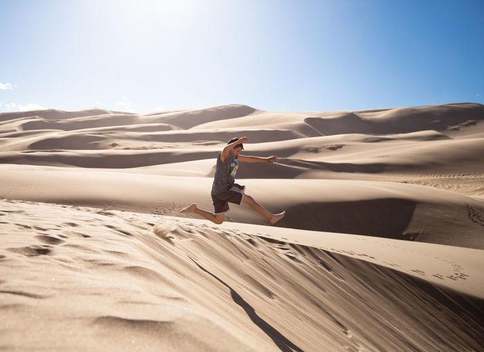 Man on sand dune in desert against sky