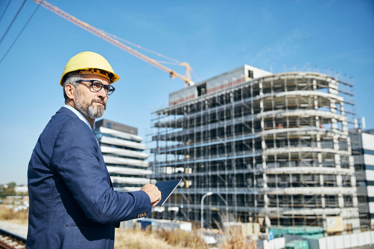 Businessman wearing hardhat while standing against built structure
