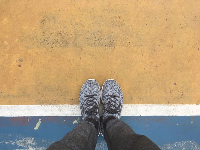 Standing on the line, from the blue place to the yellow place, go to the new place or stay at the same, change your mind concept Place Same  Low Section Human Leg Shoe Personal Perspective One Person Human Body Part Real People Standing Outdoors High Angle View
