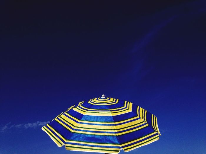 Low angle view of parasol against blue sky