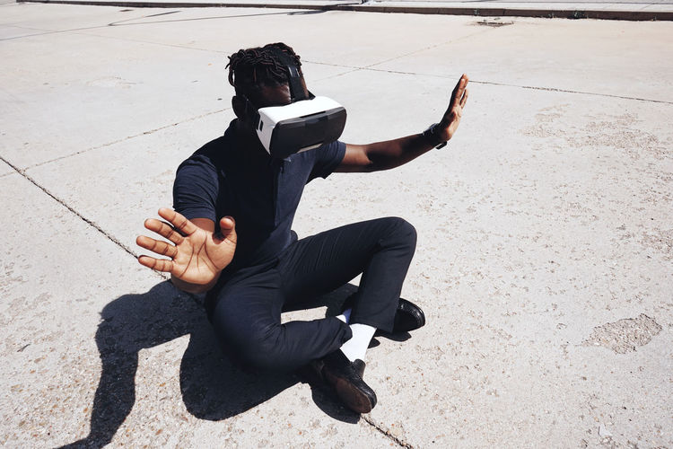 High angle view of teenager gesturing while using virtual reality on road during sunny day