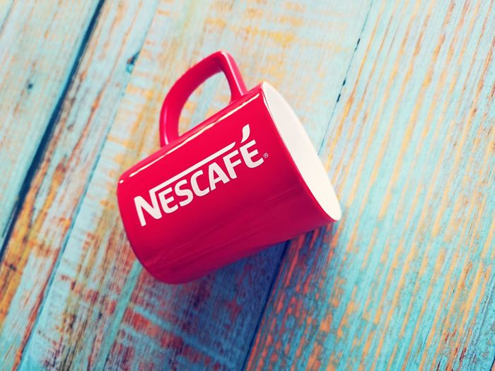 NESCAFE mug over blue wooden background with selective focus. Mug Nescafe Object Selective Focus Attractions❤️ Color Red Color Mug Brown Color Red Communication Text Single Object Close-up The Mobile Photographer - 2019 EyeEm Awards