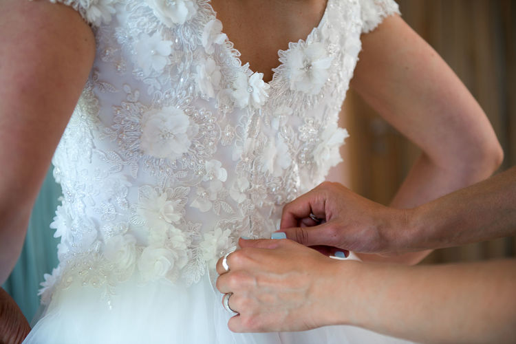 Cropped hands of woman helping bride in getting dressed