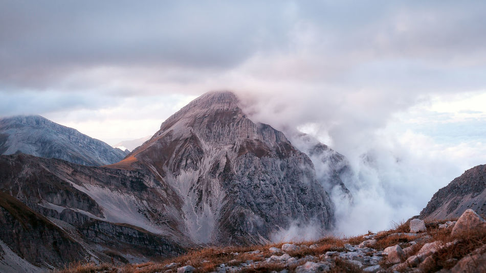 The peak of the Gran Sasso of Italy, surrounded by clouds. In the foreground some pebbles on the top front, and the other mountains in the background. Beauty In Nature Cloud - Sky Day Landscape Mountain Mountain Peak Mountain Range No People Outdoors Scenics Sky Summit View Top View