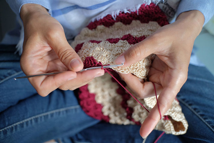 Craftsman is actively knitting using nylon yarn and knitting tools