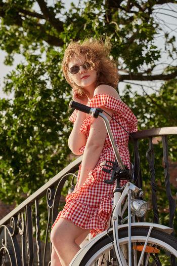 Woman sitting on railing against trees