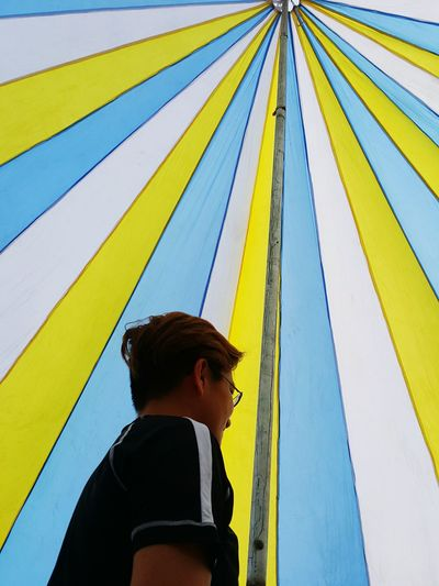 Low angle view of man looking away while standing inside tent