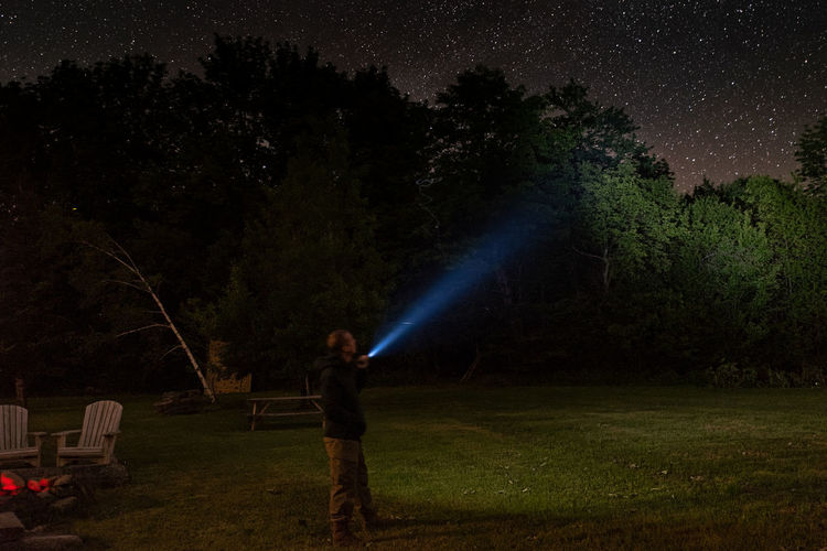 Man Holding Illuminated Flashlight While Standing In Forest At Night