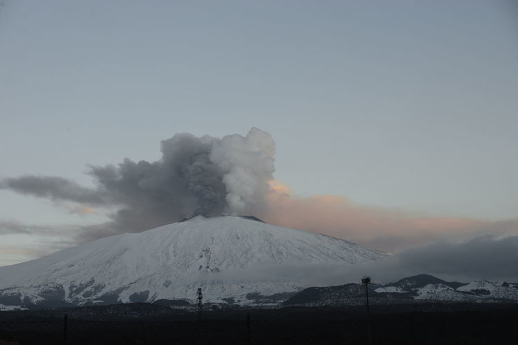 Scenic view of snowcapped mountains against sky etna eruption