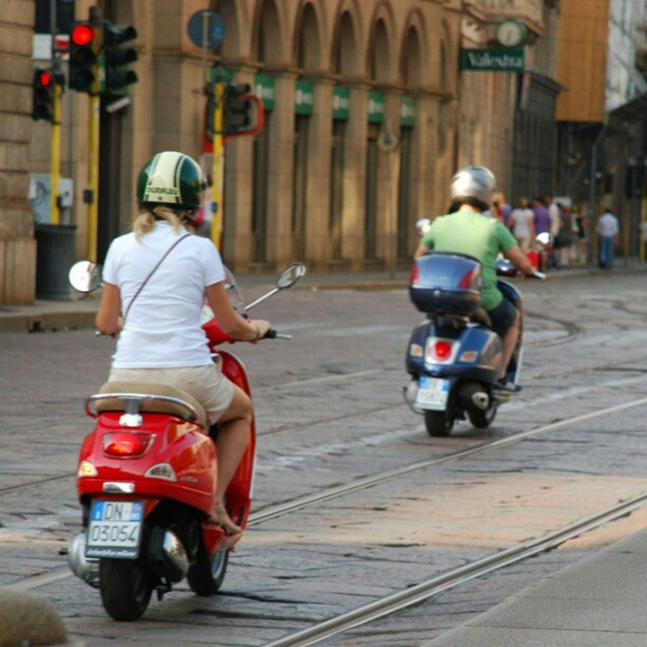 street, motorcycle, architecture, helmet, transportation, sitting, built structure, building exterior, city street, city, mode of transport, travel, crash helmet, outdoors, full length, city life, headwear, land vehicle, day, adult, travel destinations, people, two people, men, adults only, only men, young adult