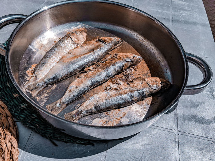 fried sardines in the pan Sardines Fish Whole Fish Fishes Fried Frying Pan Freshly Cooked Sunlight Sunlit Natural Light Table Silver Colored Food High Angle View Close-up Still Life Ready-to-eat Fried Food Temptation Indulgence Served