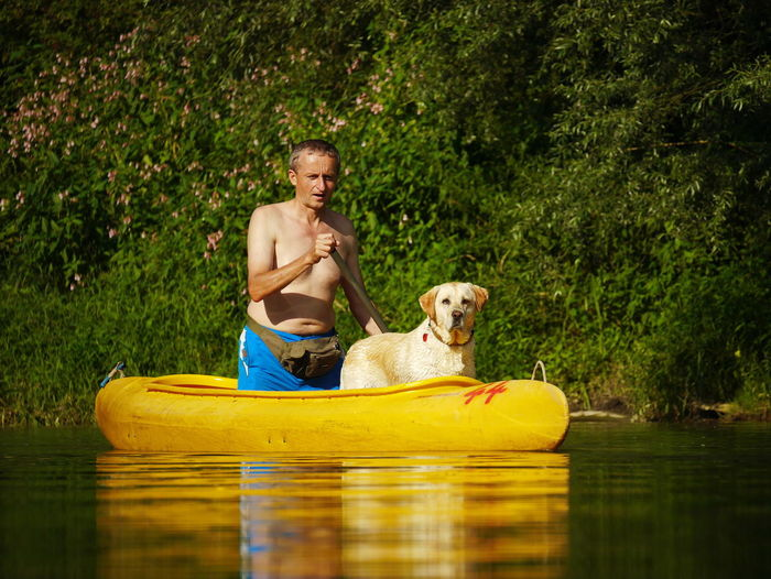 Man rowing in canoe with dog