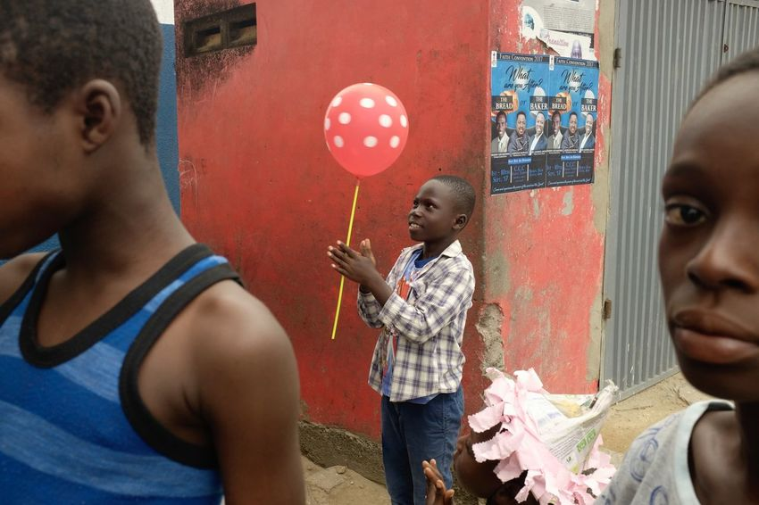 Red, Cape Coast Ghana West Africa Balloon Boys Childhood Colour Colour Of Life Face Friendship Girl Girls Playing Real People Standing Street Street Photography Street Scene Togetherness The Street Photographer - 2018 EyeEm Awards