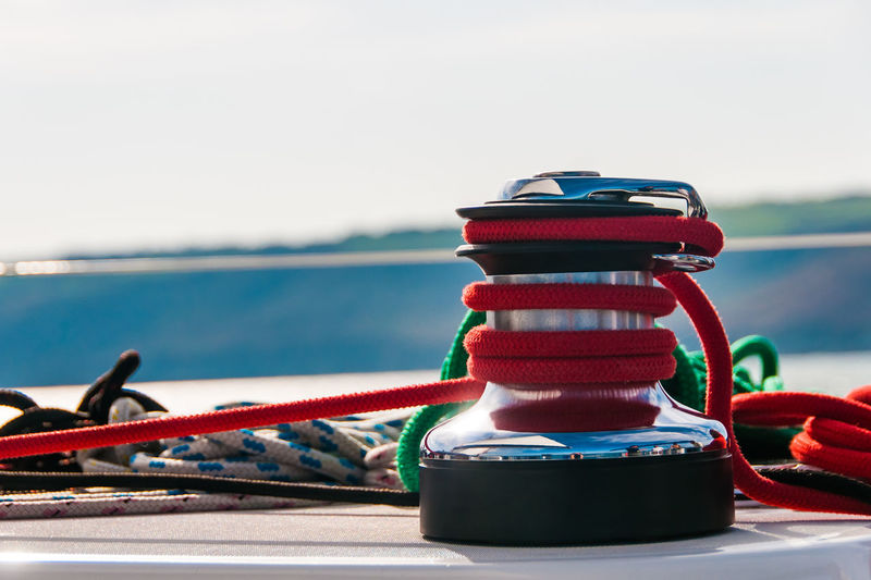 Close-up of rope tied to boat moored in sea against sky