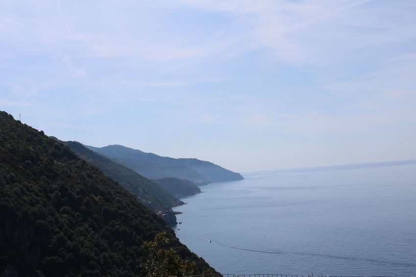 Clear fading blue sea and sky merging into one beyond the cliffs in Cinque Terre, Italy Cinque Terre Fade Hills Monterosso Al Mare Nature Sunlight Travel Blue Clear Cliffside Clouds Distant Europe Greenery Hiking Trail Horizon Italy Monochrome Ocean Sea Shore Sky Slope Trekking Path Water