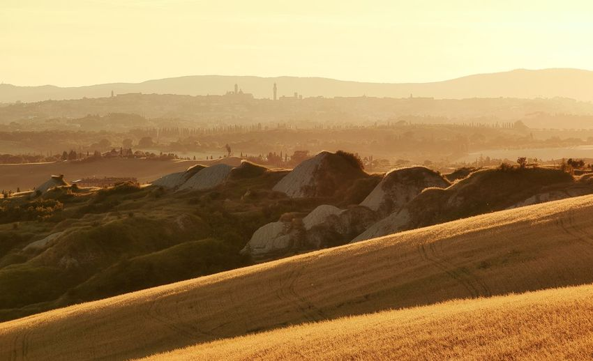 Scenic view  of tuscan clay hills  and mountains in golden light . siena towers in the background .