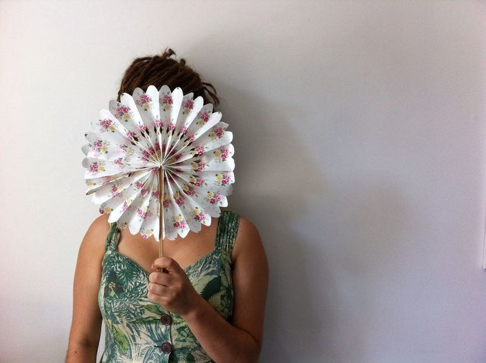 Woman hiding face with hand fan against white wall