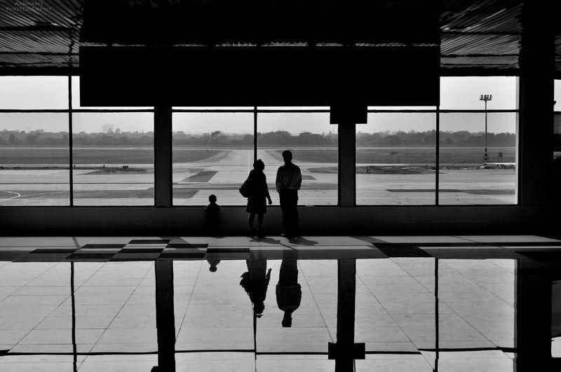 People Reflecting In Glass Floor, Airport Building Interior