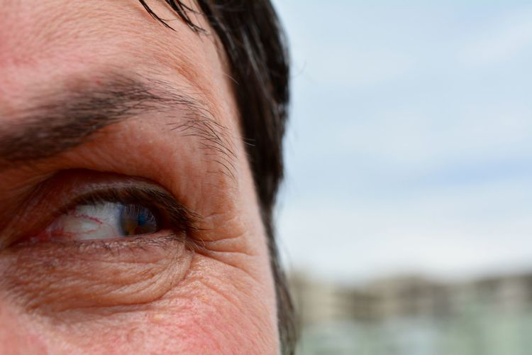 Cropped image of woman eye against sky