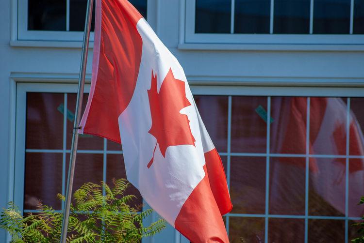Canadian flag against sky seen through window