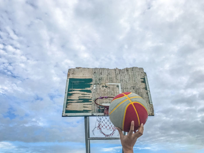 Cropped hand of person making basket against cloudy sky