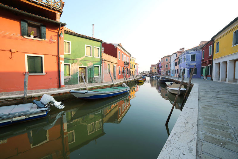 Boats moored on the waterway and reflection on the water of the colorful houses of the island of Burano near Venice in Italy Burano, Italy Colored Houses Houses Architecture Building Exterior Built Structure Burano Canal Colored House Coloured Houses House Island Isle Italian Italy Mode Of Transport Moored Nautical Vessel Outdoors Reflection Residential Building Transportation Venice Water Window