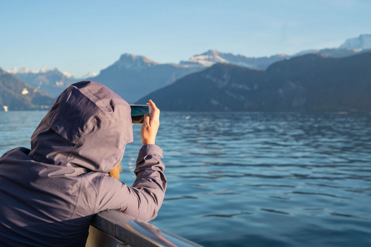 Close-Up Of Woman Photographing Sea Through Mobile Phone Against Mountain