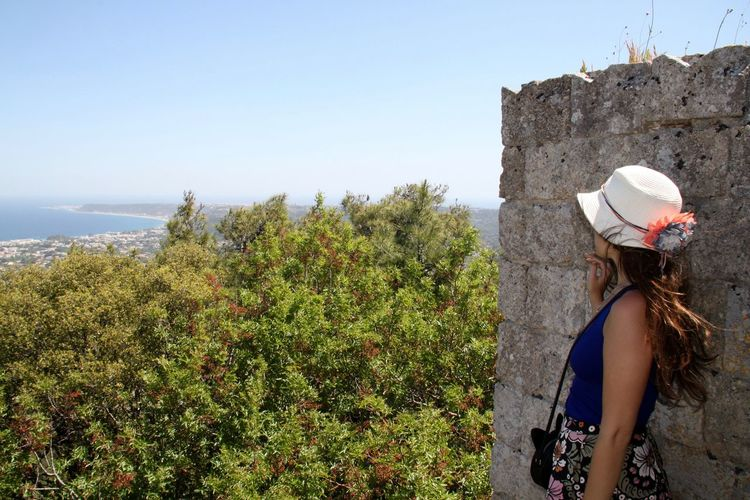 Woman leaning on wall against sky at rhodes