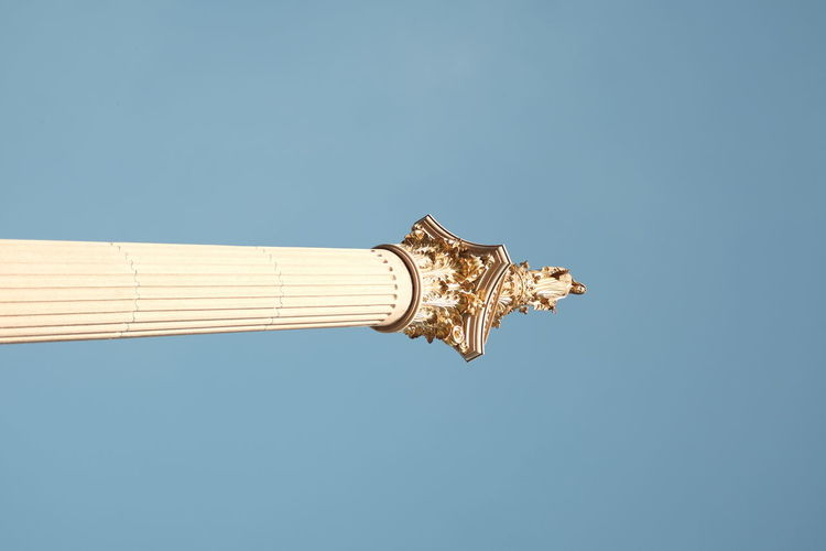 Low angle view of cross against building against clear blue sky