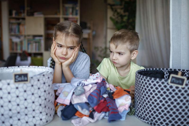 Cute sibling looking at dirty clothes