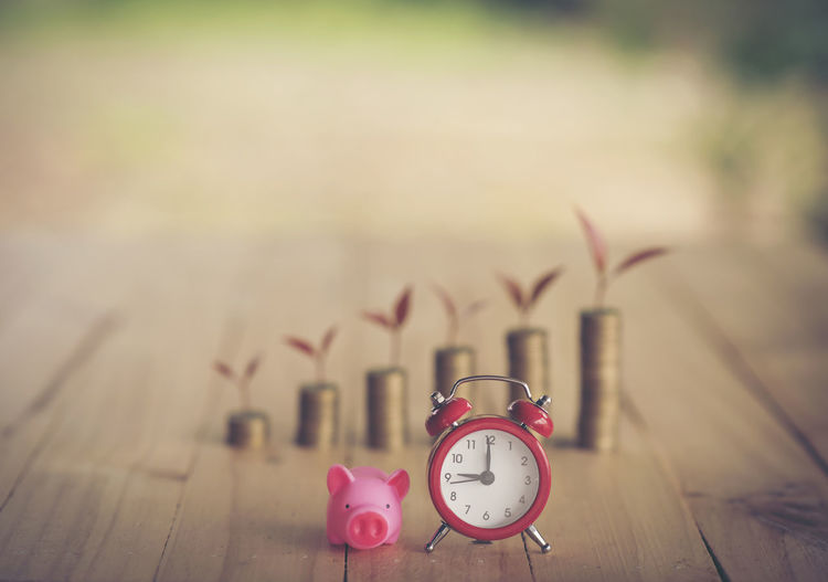 Stacked coins with piggy bank and alarm clock on table