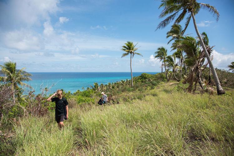 Boys Walking Amidst Plants On Field Against Sea