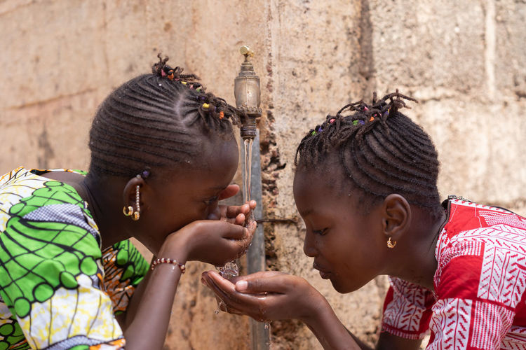 Girls drinking water from faucet against wall