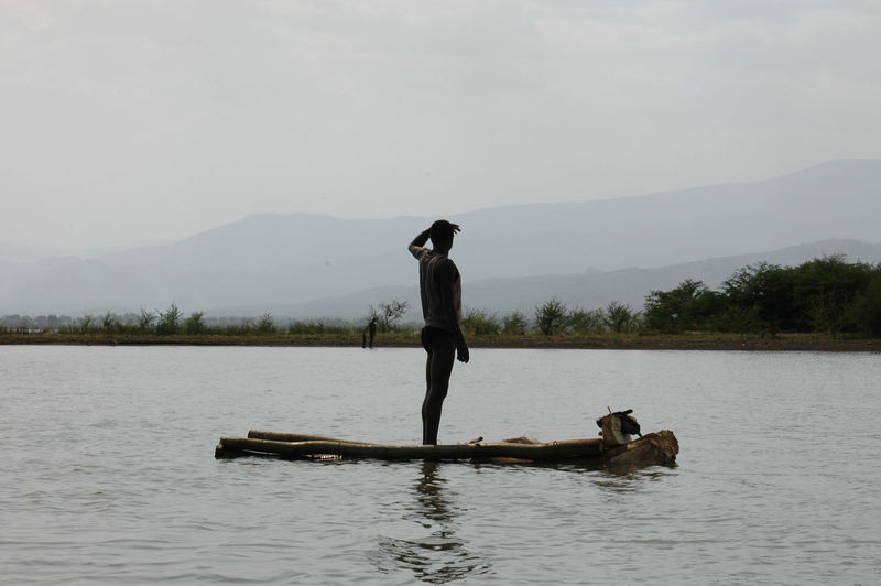 Man standing on wooden raft in lake against sky