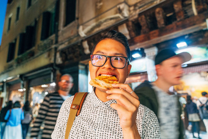 Close-up portrait of man eating in city