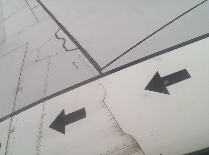 Low angle view of arrow sign on wall