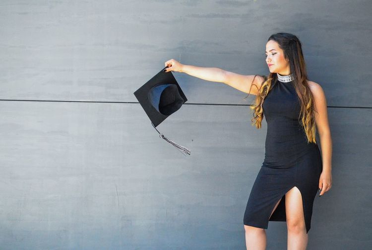 Woman holding mortarboard while standing against wall