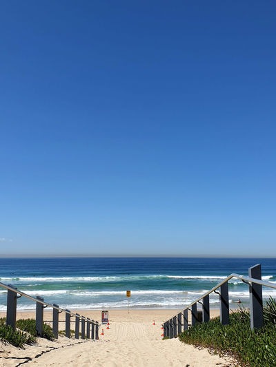 Scenic view of beach against clear blue sky