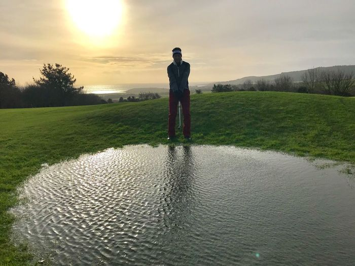 Man with golf club standing by water course