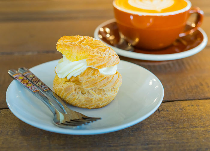 Choux Cream with hot coffee Bekery Dessert Cake Cake And Coffee Choux Cream Latte Coffee Coffee - Drink Coffee Cup Crockery Cup Drink Food Food And Drink Freshness Indoors  Indulgence Latte Coffee No People Plate Ready-to-eat Refreshment Still Life Sweet Food Table Temptation