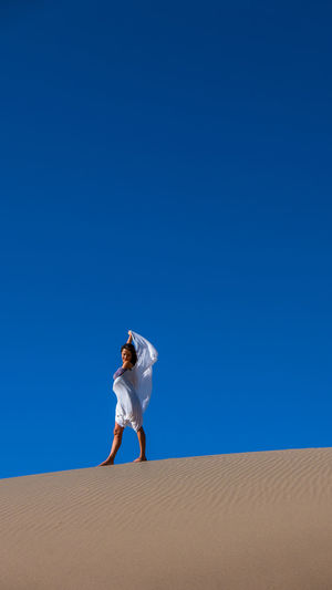 Young woman standing on sand at desert against clear blue sky