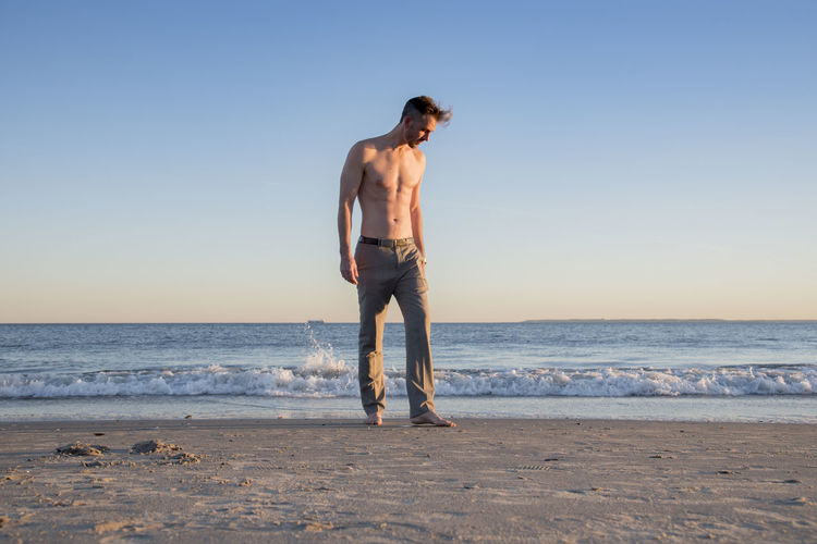 Full length of shirtless man standing on shore at beach