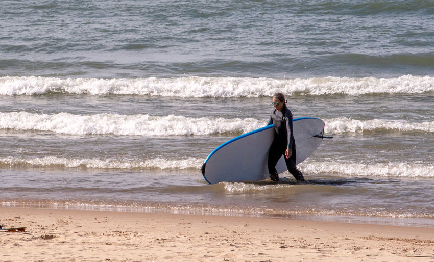 Rear view of man with surfboard at beach